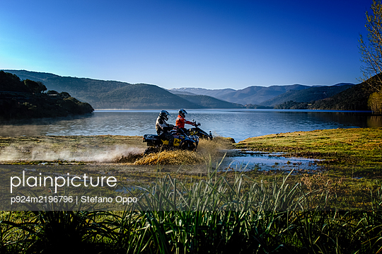 Two people riding motorcycles through shallows on Gusana lake, an artificial lake in the territory of Gavoi, Sardinia, Italy.  - p924m2196796 by Stefano Oppo