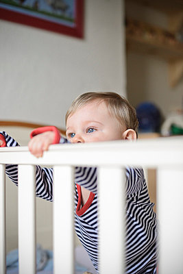 Baby boy peeping over cot rail  - p1072m829232 by Neville Mountford-Hoare