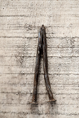 Two bent, rusty old nails on rough sawn timber. - p1433m1574954 by Wolf Kettler
