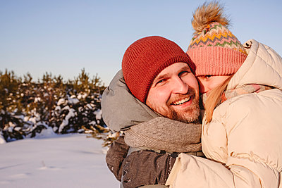 Smiling father embracing daughter in warm clothing during winter - p300m2265972 by Ekaterina Yakunina