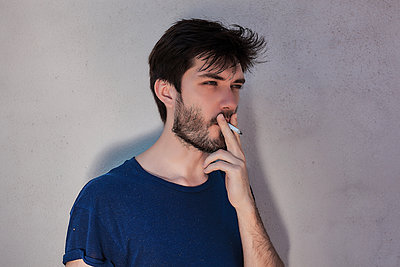 Young man with beard smoking cigarette in front of cement wall - p429m1494608 by Rehulian Yevhen