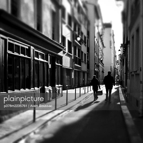 Two pedestrians in narrow street - p378m2235761 by Alain Boussac