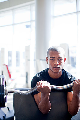 Portrait of determined young man lifting barbell in gym - p1166m1473598 by Cavan Images