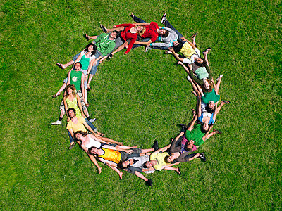 Group lying on grass in a circle - p4290911f by Dev Carr