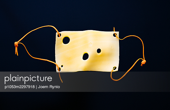 Slice of cheese in the shape of a medical mask - p1053m2297918 by Joern Rynio