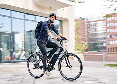 Bicycle courier riding an electric bike - p1124m2052980 by Willing-Holtz