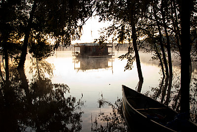 A canoe and a house boat at dusk on a river with mist. - p1424m1501954 by Michael Hanson