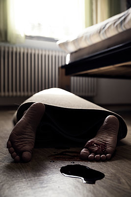 Corpse of woman rolled up in a carpet lying on floor of sleeping room - p300m1060679 by Miriam Dörr