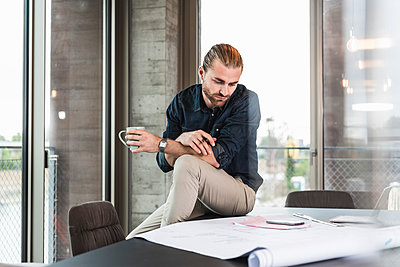 Young businessman looking at plan on desk in office - p300m2043196 by Uwe Umstätter