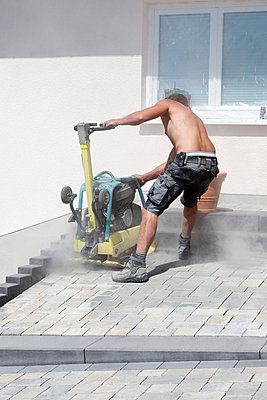 Young man paving stones with vibrator - p300m798173f by Dieter Heinemann