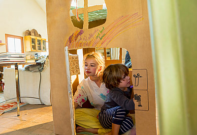 Caucasian boy and girl playing in cardboard house - p555m1491627 by Marc Romanelli