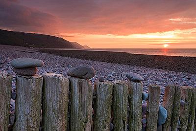 Pebbles on wooden posts at sunset, Bossington Beach, Exmoor National Park, Somerset, England, United Kingdom, Europe - p871m1048047 by Adam Burton