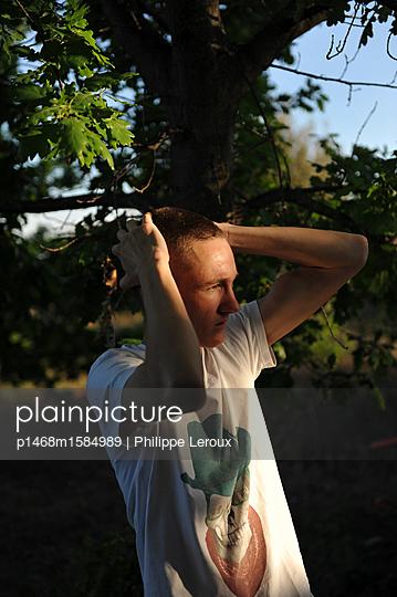 Jugendlicher mit Händen auf dem Kopf im Freien - p1468m1584989 von Philippe Leroux