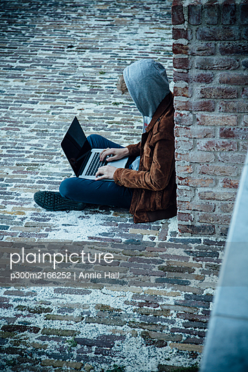 Teenager using laptop and sitting on a stone floor in the city - p300m2166252 by Annie Hall