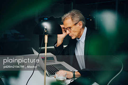 Worried senior businessman working late while sitting with laptop at coworking space - p426m2194788 by Maskot