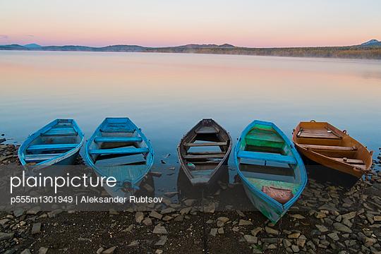 Five empty rowboats on rocky shore of lake at sunset - p555m1301949 by Aleksander Rubtsov