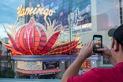 Man with smartphone takes a picture in Las vegas - p1057m1466821 by Stephen Shepherd
