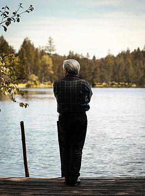 Älterer Mann steht am Seeufer - p1324m1165206 von michaelhopf
