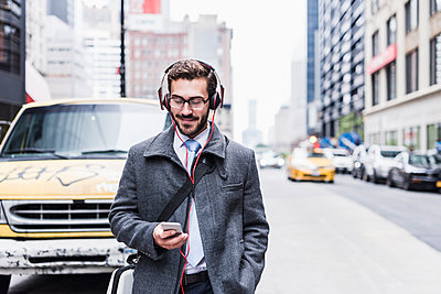 USA, New York City, businessman with cell phone and headphones on the go - p300m1191812 by Uwe Umstätter