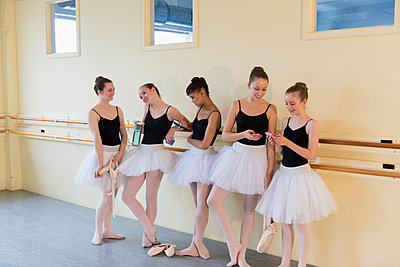 Girls talking and texting on cell phones in ballet studio - p555m1491101 by Mark Edward Atkinson