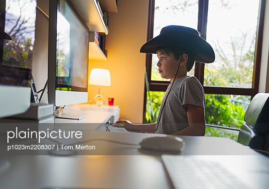 Cute boy in cowboy hat playing video game at computer in home office - p1023m2208307 by Tom Merton