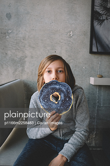 Long Haired Boy Peeks over Giant Donut - p1166m2258483 by Cavan Images