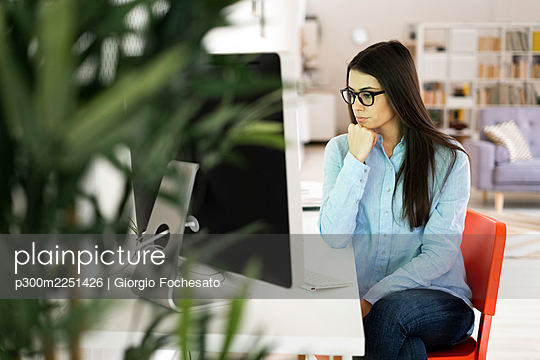 Thoughtful businesswoman with hand on chin looking away while sitting at office - p300m2251426 by Giorgio Fochesato
