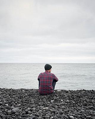 Mann sitzt am Steinstrand - p1124m1060218 von Willing-Holtz