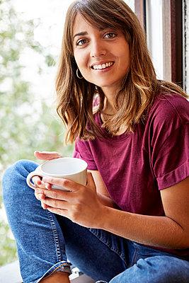 Junge Frau auf der Fensterbank mit einer Tasse Tee - p1146m1503087 von Stephanie Uhlenbrock