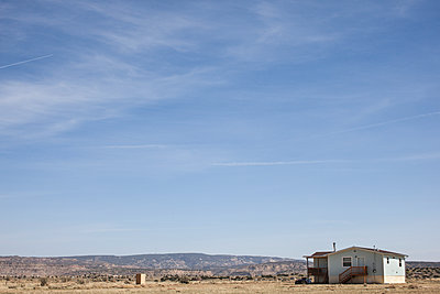 blue frame house on open plain against mountaineous background - p1291m1548095 by Marcus Bastel