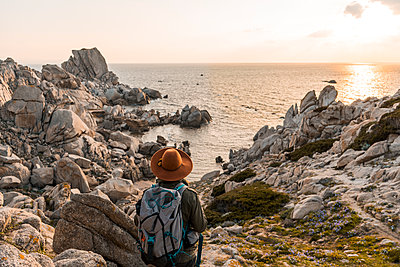 Italy, Sardinia, back view of hiker with backpack looking to the sea - p300m1580769 von VITTA GALLERY