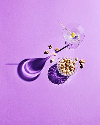 Directly above shot of pistachios and martini glass with shadow on purple background - p300m2144012 by Kai Schwabe