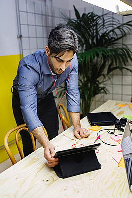 Young man using digital tablet at desk in creative office - p426m1407158 by Maskot