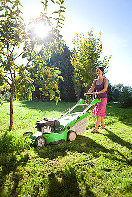 woman mowing the lawn - p4299870f by Sandra Steh