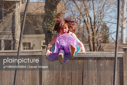 Little girl with missing teeth and colorful dress jumps on trampoline - p1166m2250664 by Cavan Images