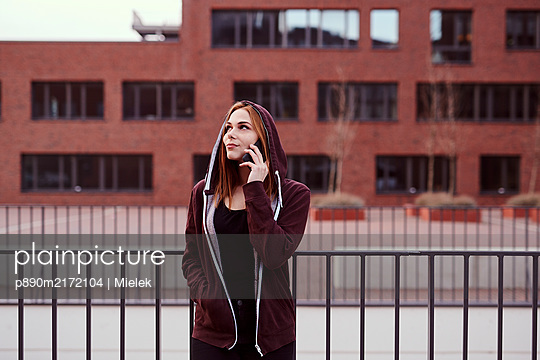 Young woman with smartphone and hooded jacket - p890m2172104 by Mielek
