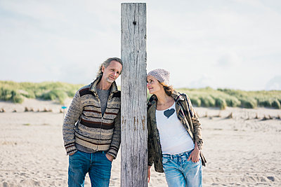Mature couple on the beach, leaning on wood pole - p300m2059513 von Robijn Page