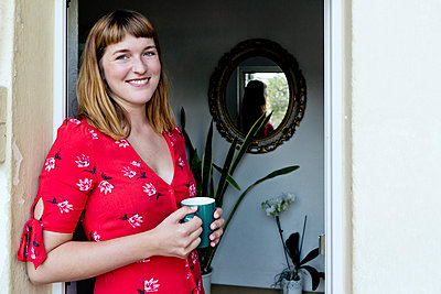 Portrait of smiling young woman with cup of coffee standing on balcony - p300m2131852 by FL photography