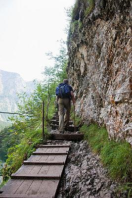 Man hiking uphill - p42911226f by Stefanie Grewel