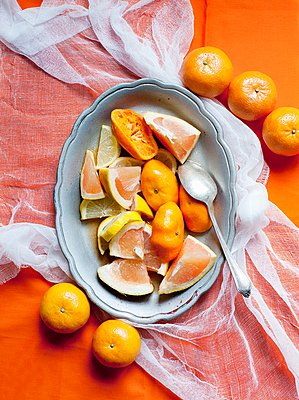 Dish of sliced pink grapefruit, lemon, orange and tangerines - p429m1029673 by Magdalena Niemczyk - ElanArt