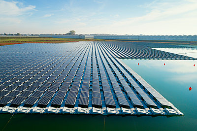 Floating solar panels installed on water supply of neighbouring greenhouses, elevated view, Netherlands - p429m2058276 by Mischa Keijser