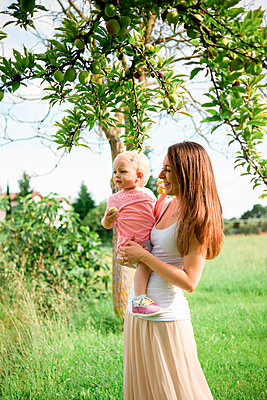 Mother carrying toddler daughter under fruit tree, Arezzo, Tuscany, Italy - p429m2098230 by Senserini Lucrezia