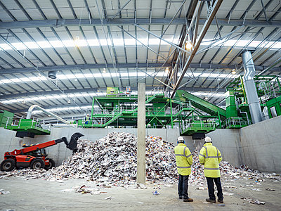 Workers inspecting waste paper in waste recycling plant. - p429m2202283 by Monty Rakusen