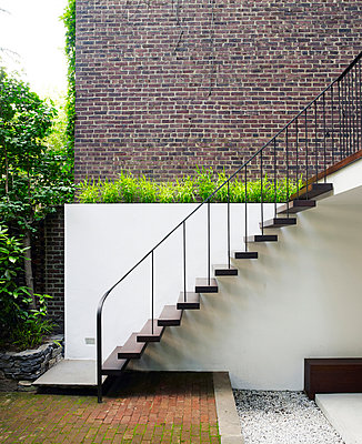Wooden steps with metal handrail in garden of Chelsea Townhouse, New York, USA - p855m909105 by Richard Powers