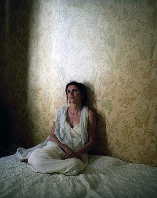 Woman sitting on bed - p945m2125800 by aurelia frey