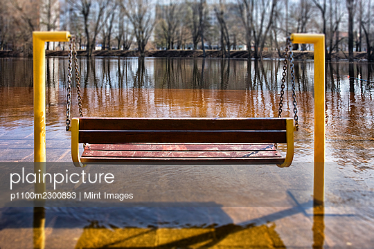 Empty hanging bench swing surrounded by hard frozen ice, riverbank - p1100m2300893 by Mint Images