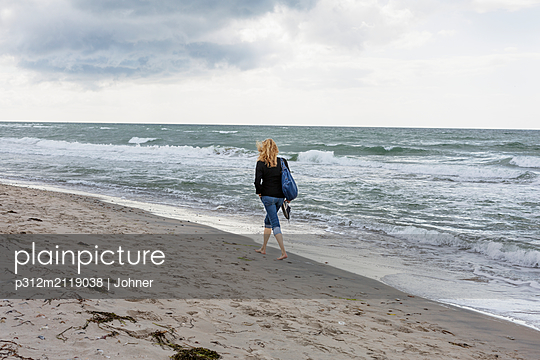 Woman walking on beach - p312m2119038 by Johner
