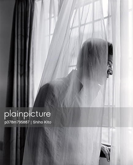 Young man through curtains - p378m795887 by Shiho Kito