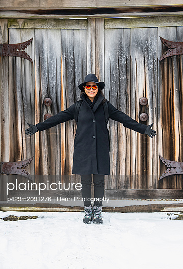 Woman standing in front of wooden gate, Takayama, Gifu, Japan - p429m2091276 by Henn Photography