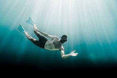 Full length of man swimming underwater in the ocean facing camera - p1166m2137815 by Cavan Images